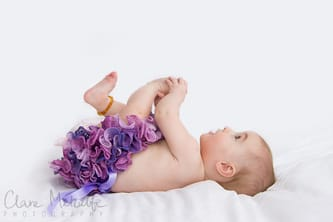 Baby grabbing feet with frilly knickers