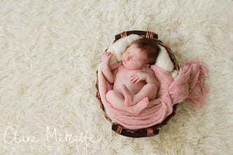 newborn baby girl asleep in basket