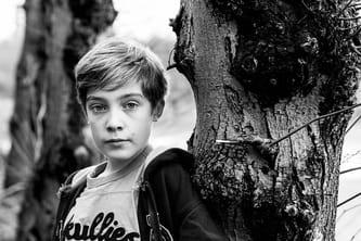 Black and white photograph of boy standing next to tree.