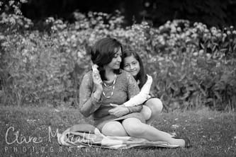 Black and white photograph of mother and daughter sitting on grass with flowers behind.