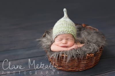 Newborn asleep in basket wearing pixie hat