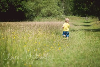 Photograph of child walking away in field of buttercups.