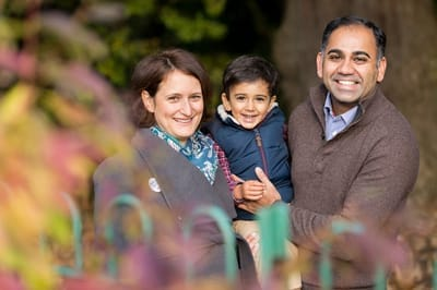 Autumnal photograph of family smiling in a park in Ealing.