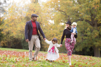 Photograph of a family walking through autumn leaves in park Eastcote