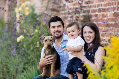 Photograph of family with baby and dog sitting in a walled garden.