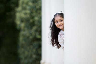 Photograph of girl looking out from behind pillar at Kenwood House.