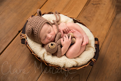 Newborn baby dressed as teddy bear asleep in a basket