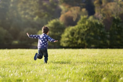 Photograph of a boy pretending to be an airplane in a field.