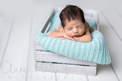 Newborn baby asleep in crate