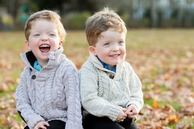 Photograph of twin boys laughing in autumnal scene.